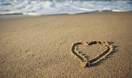 Sandy beach with a heart and waves, Royalty Free Stock Images