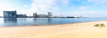 Sandy beach with industry on the other bank of the river . Grass Stock Photos