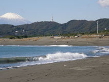 Sandy beach in Japan with Mount Fuji on the horizon. Sandy beach on a coast of the Pacific Ocean in Hiratsuka town, Kanagawa Prefecture, Japan, with wooded hills Stock Photo