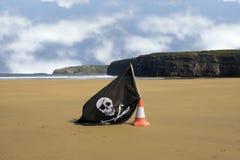 Sandy beach with jolly roger flag Stock Photos