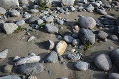 Sandy beach with large boulders royalty free stock photo