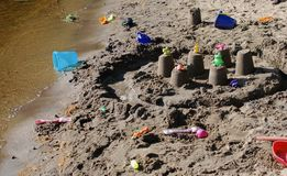 Sandy beach covered in childrens` sand toys royalty free stock image