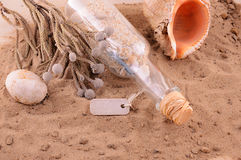 Sandy beach with letter in bottle and shells. Royalty Free Stock Image