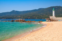 Sandy beach and lighthouse, Propriano, Corsica. Sandy beach and lighthouse tower. Coastal landscape of Propriano town, Corsica island, France Stock Photos