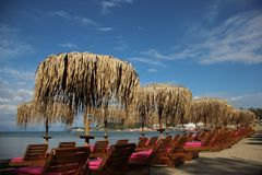 Quiet Sandy Beach With Palm Leaves Umbrella And Sunny. Sea Front In Summertime. Sandy Beach With Local Palm Leaves Umbrella And Sun Beds  On Sidari Corfu Greece royalty free stock images