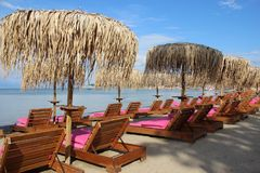 Quiet Sandy Beach With Local Umbrella And Sunny. Sea Front In Summertime. Sandy Beach With Local Palm Leaves Umbrella And Sun Beds  On Sidari Corfu Greece stock photography