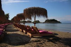 Quiet Sandy Beach With Umbrella And Beach Chair. Sea Front In Summertime. Sandy Beach With Local Palm Leaves Umbrella And Sun Beds  On Sidari Corfu Greece stock images