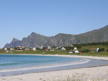 Sandy beach in Lofoten islands, Norway. Sandy beach on a coast of the Arctic Ocean in Norway (Lofoten islands); cottages in green meadows and hills on the Stock Image