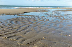 Sandy beach at low tide. A beach with attractive patterns in the sand at low tide at Tauranga, Bay of Plenty, New Zealand Royalty Free Stock Photo