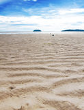 sandy beach at low tide with blue skies Royalty Free Stock Image