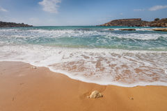 Sandy beach on the Malta island. The sandy beach below the rocky cliffs of the Malta island Stock Photos