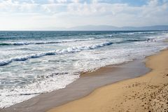 Sandy beach in Manhattan Beach California. Waves roll in. On the sand royalty free stock image