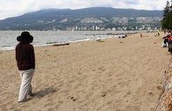 Sandy Beach med staden i bakgrund Arkivbild