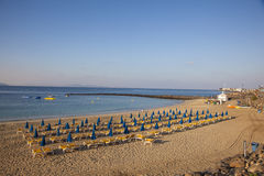 Sandy beach in the morning with sunloungers and parasols Royalty Free Stock Photo