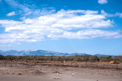Sandy beach, mountains and blue sky. Royalty Free Stock Photo