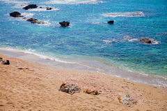 Sandy beach near azure sea Stock Photos