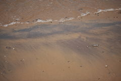 Sandy beach and ocean. Close up of waves lapping sandy beach Stock Images