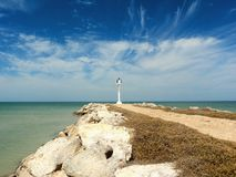 Sandy beach and ocean panorama whith a lighthouse Stock Images