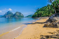 Sandy Beach with Palm Shadows, Huge Rocks in Background, El Nido, Palawan, Philippines Royalty Free Stock Photography