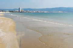 A sandy beach and a panoramic view of the coast of the Bulgarian. A sandy beach with clear sea water and a panoramic view of the coast of the Bulgarian resort of Stock Photos