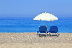 Sandy beach with parasol and two sunbeds Royalty Free Stock Photo