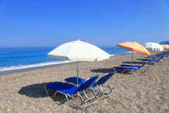 Sandy beach with parasols and sunbeds Stock Images