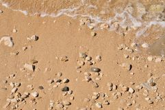 Sandy beach with pebbles and wave Royalty Free Stock Photos
