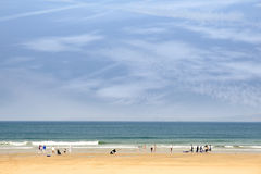 Sandy beach with people going to surf Stock Image