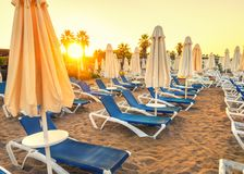 Beach without people and with sun loungers, folded umbrellas, palm trees, Turkey, Side resort. Sandy beach without people and with sun loungers, folded umbrellas royalty free stock images