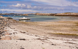 Sandy beach, a pier on the fjord, moored boat Stock Image