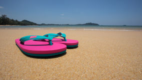 sandy beach and pink sandals Stock Photos