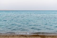 Sandy beach on the Red Sea. Low waves in the evening in the bay of Hurghada royalty free stock image
