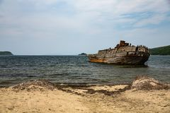 Sandy beach and the remains of a sunken ship in the Japanese sea royalty free stock image