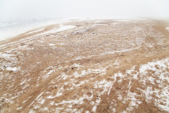 Sandy beach by the river in the fog in winter Stock Image