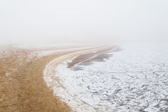 Sandy beach by the river in the fog in winter Stock Photo