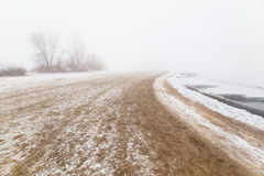 Sandy beach by the river in the fog in winter Stock Photos