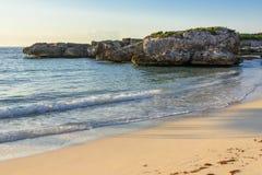 Sandy beach, rocks, and sea. Riviera Maya, Cancun, Mexico. Sandy beach, rocks, and sea under blue sky. Riviera Maya, Cancun, Mexico Royalty Free Stock Photo