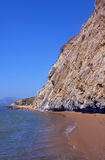 Sandy beach and rocky cliff Stock Photography