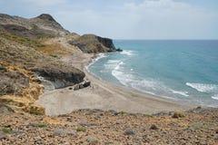 Sandy beach rocky coast natural park Almeria Spain. Secluded sandy beach on rocky coast in the Cabo de Gata-Níjar natural park, Playa del Barronal royalty free stock image