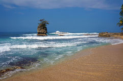 Sandy beach with rocky islet stock images