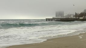 Sandy beach and rough sea,pier and high-rise hotel building in fog,dense clouds stock video footage
