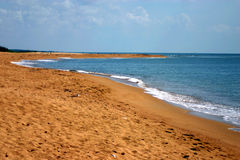 Sandy beach and sea. Scenic view of sandy beach receding into distance next to blue sea Royalty Free Stock Photography