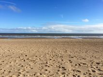 Sandy Beach with sea and sky. A sand beach with distant sea on a sunny day Stock Images