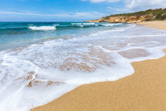 Sandy beach sea waves and mountain at coast Royalty Free Stock Images