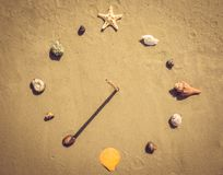 Sandy beach, seashells and sundial. Summer vacation on the sea coast. Beautiful sundial from sea shells and reeds. Summer sandy beach royalty free stock image