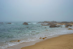 Sandy beach shore sea ocean water with rocks and stones during fog Stock Image