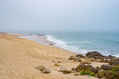 Sandy beach shore sea ocean water with rocks and stones during fog Royalty Free Stock Photo
