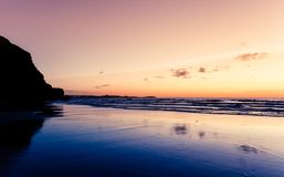 Sunset above Watergate Bay. A sandy beach and a silhouetted rock at sunset above Watergate Bay, Newquay, Cornwall, England stock photos