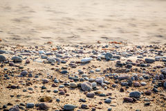 Sandy beach with small pebbles and smooth water, selective focus. Stock Photo
