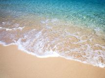 Sandy beach with a soft wave and blue ocean with crystal water. Stock Photography